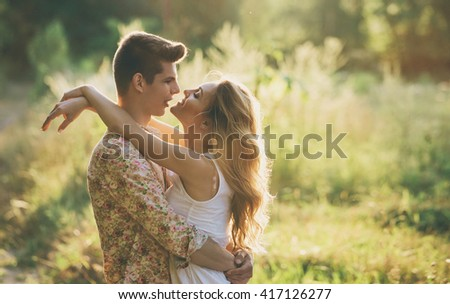 Love and romance. Outdoor portrait of beautiful loving couple kissing in park. - stock photo