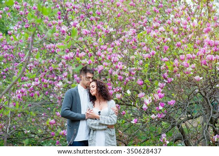 Love and tenderness. Beautiful young loving couple embracing in blossom spring garden. Romantic dating. - stock photo