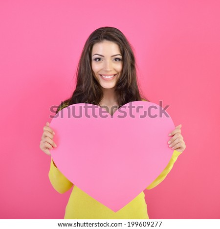 Love and valentines day woman holding heart and smiling over pink background. Beautiful woman in love.  - stock photo