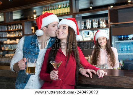 Love beer and Christmas. Loving couple is kissing in a bar or pub, wearing New Year Santa Claus hats. Girls bartender also is wearing Santa Christmas hat and stays on a background - stock photo