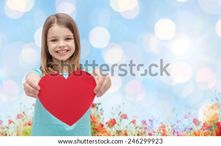 love, charity, holidays, children and people concept - smiling little girl with red heart over blue lights and poppy field background - stock photo