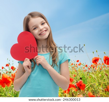 love, charity, holidays, children and people concept - smiling little girl with red heart over blue sky and poppy field background - stock photo