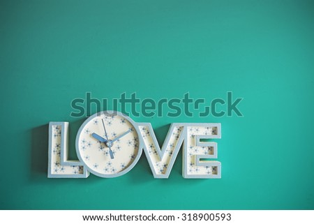 Love clock on mint green background with copy space. Vintage effect. Concept of Love. - stock photo