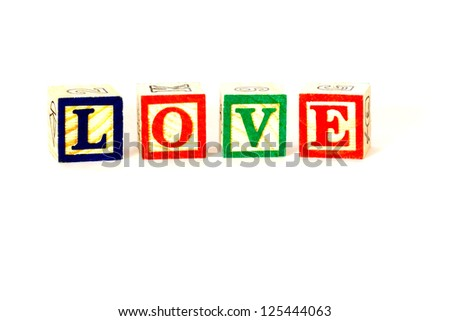 love, colourful letters printed on wooden blocks made into the word love, isolated on white. - stock photo