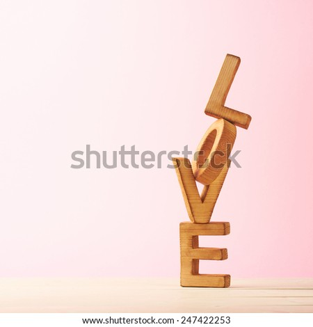 Love composition of wooden block letters agains the pink background - stock photo