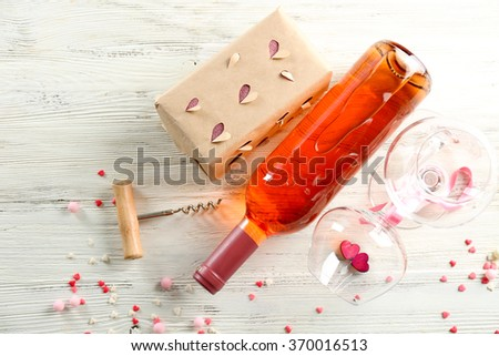 Love concept - wine bottle with decorations on white wooden background, close up - stock photo