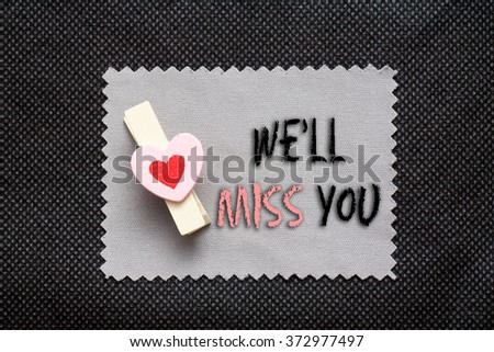 "Love conceptual background with wood clips,love shape on grey paper ""We'll miss you"" - stock photo"