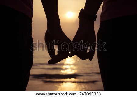 love couple holding hands fingers at sunset on the beach, valentine day - stock photo