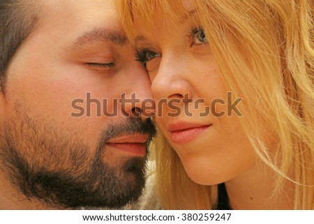 love -  couple in love close up  - man holding his face against her closing eyes caressing her with  affection and fondness to the pretty girl - moment of tenderness - focus on man's eyes - stock photo
