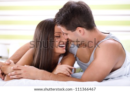 Love couple lying in bed kissing and looking each other - stock photo