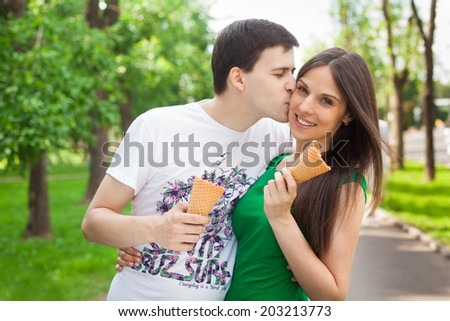 love couple out in the park with ice cream kissing in the open air - stock photo