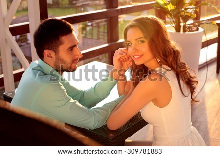 love couple sitting at a restaurant talking on the summer terrace holding each other 's hand and admire the sunset - stock photo