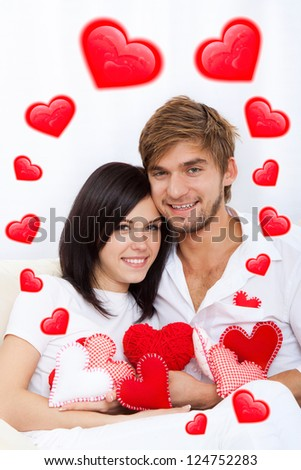love couple valentine day heart shape, holding lot of red valentine's heart together sitting on couch at home, excited happy smile, hug, concept hearts flying around - stock photo