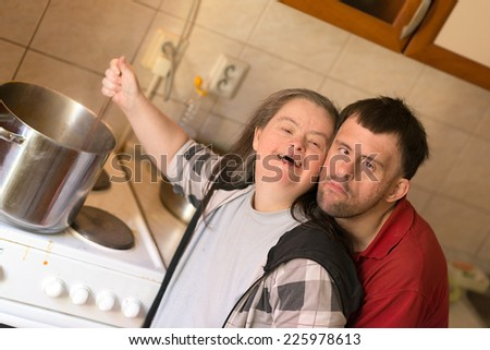 love couple with down syndrome in kitchen - stock photo