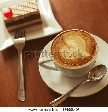 Love cup and art coffee concept. Heart drawing on latte (capuccino). Coffee cake with red jelly (chocolate biscuit). Daylight. Close up. Indoor shot - stock photo