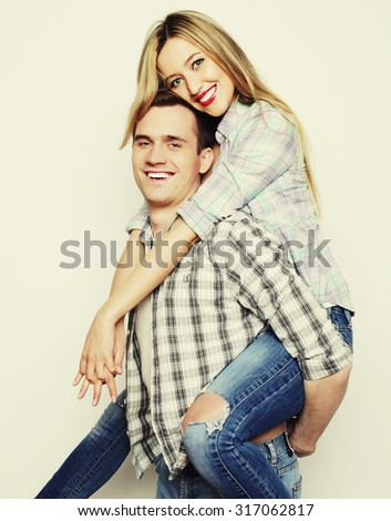 love, family and people concept:   lovely couple,  young man carrying girlfriend on his back. - stock photo