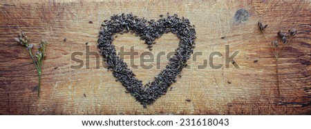 Love for caraway: carum carvi seeds arranged in heart shape on old wooden cutting board  - stock photo