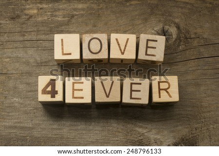 love forever text on a vintage cubes on a wooden background - stock photo
