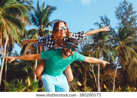 love  friendship concept smiling couple having fun over sky background embracing and kissing outdoors at summertime,man piggybacking his girlfriend while keeping arms outstretched Close up portrait  - stock photo