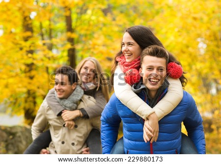 love, friendship, family and people concept - smiling friends having fun in autumn park - stock photo