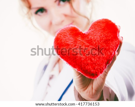 Love from working and helping people. Mid age blonde doctor in white medical apron with heart. Enjoy work concept. Isolated on white. - stock photo
