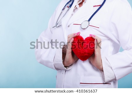 Love from working and helping people. Part body female doctor in white medical apron with heart on blue. Enjoy work concept. - stock photo