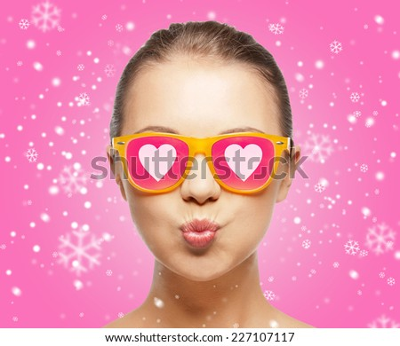 love, happiness, holidays, christmas and people concept - smiling teenage girl in sunglasses with hearts over pink background - stock photo