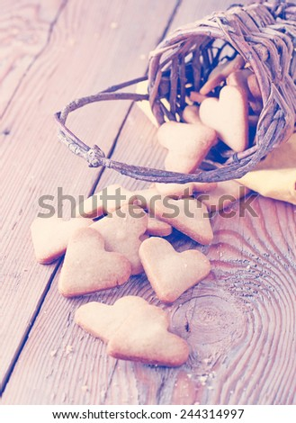 Love, happy, home, food, still life concept. Handmade heart cookies for Valentine's day in a basket on a wooden table. Selective focus. Vintage style, toned image - stock photo