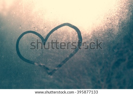 Love heart shape hand drawn on wet, frozen window pane with morning sunlight background. Selective focus used. - stock photo