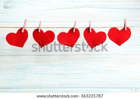 Love hearts hanging on rope on a blue wooden background - stock photo