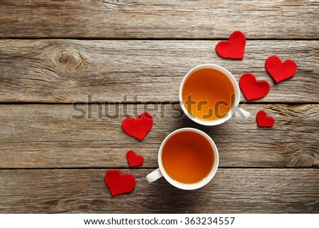 Love hearts with cups of tea on a grey wooden table - stock photo