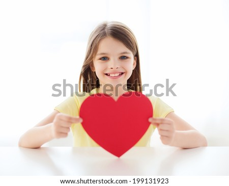 love, home, happiness and people concept - smiling little girl with red heart at home - stock photo