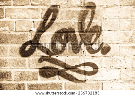 Love in graffiti paint on a brick wall with sepia filter - stock photo