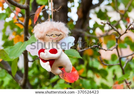 Love in the air.  Handmade figure of Angel hanging in autumn garden. selective focus, shallow dof - stock photo