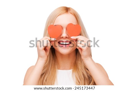Love is a great feeling! Beautiful young blond hair woman holding heart shaped valentine cards in front of her eyes and smiling while standing isolated on white - stock photo
