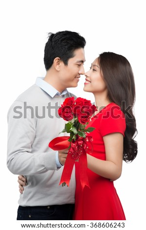 Love is a great feeling! Beautiful young loving couple bonding to each other while woman kissing her boyfriend holding bouquet of flowers - stock photo