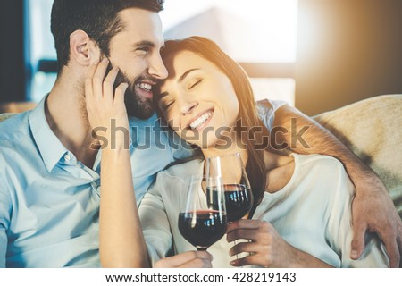 Love is a in the air. Beautiful young loving couple sitting close to each other and drinking red wine - stock photo