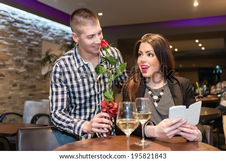 Love is in the Air. Young couple celebrating anniversary. Man with red rose suprised young woman. She is speechless and happy while smiling. - stock photo