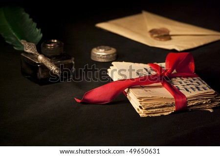 Love letter, antique quill and black ink and stack of letters tied with a red ribbon. - stock photo