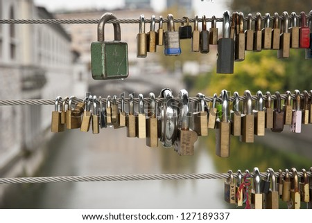 Love locks locked on the fence of the bridge in Ljubljana, Slovenia - stock photo