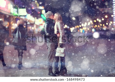 Love man and woman embracing outdoors winter snowfall - stock photo