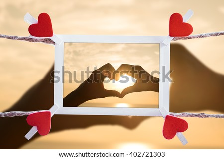 Love memories instant photo and clippaper heart hanging on the clothesline with Silhouette hand in heart on sunrise the sea.Designer concept. - stock photo
