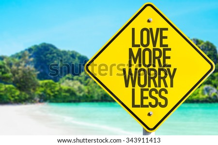 Love More Worry Less sign with beach background - stock photo