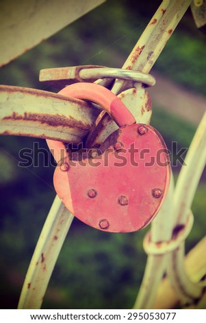 Love padlocks at a bridge while sundown. Vintage effect - stock photo