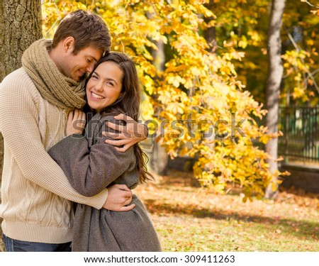 love, relationship, family, season and people concept - smiling couple hugging over autumn natural background - stock photo