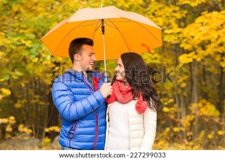 love, relationship, season, family and people concept - smiling couple with umbrella walking in autumn park - stock photo