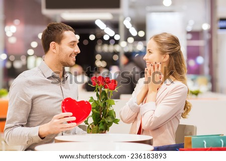 love, romance, valentines day, couple and people concept - happy young man with red flowers giving present to smiling woman at cafe in mall - stock photo