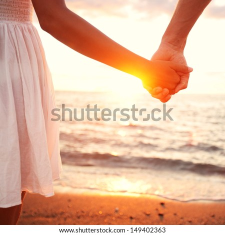 Love - romantic couple holding hands, beach sunset. Lovers or newlywed married young couple in romance on beautiful sunset at beach. Young woman and man in love walking hand in hand on beach. - stock photo