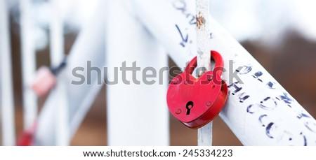 Love romantic padlocks locked on fence of the white bridge - stock photo