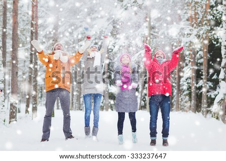 love, season, friendship and people concept - group of happy men and women having fun and playing with snow in winter forest - stock photo